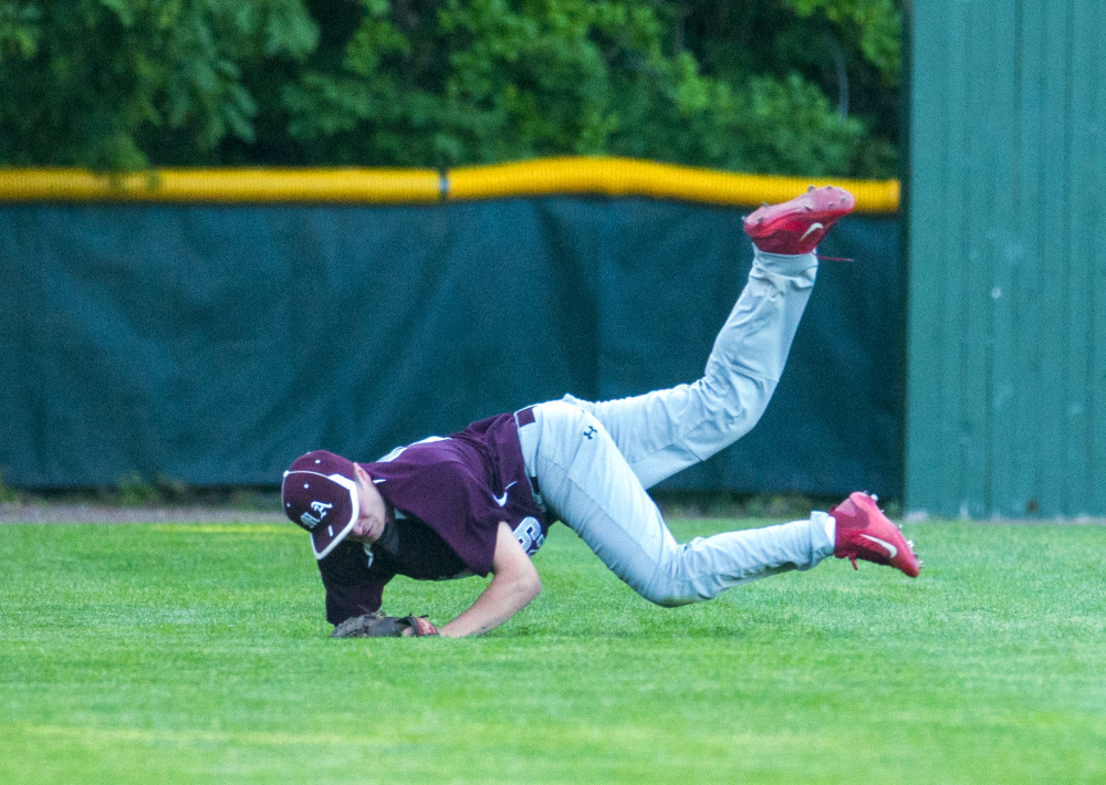 Monmouth left fielder Kane Gould somersaults in foul territory after catching a foul flyball for an out during the Class C South championship game Wednesday at St. Joseph's College in Standish.