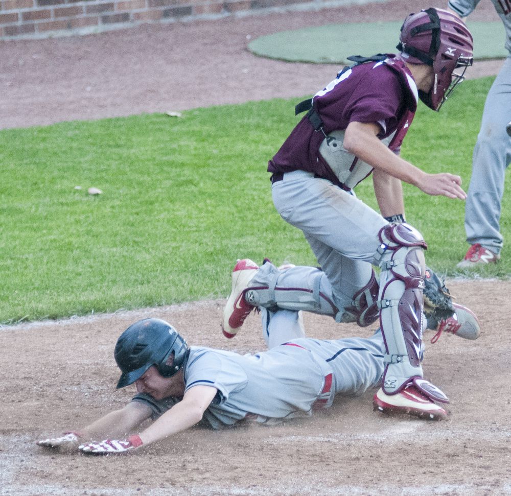 Nick Austin slides safely into home under Monmouth catcher Corey Armstrong in the Class C South championship game Wednesday at St. Joseph's College in Standish.