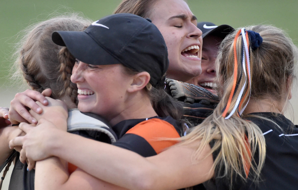 Members of the Skowhegan softball team celebrate their 5-4 win over Oxford Hills in the Class North championship game Wednesday at Cony High School.