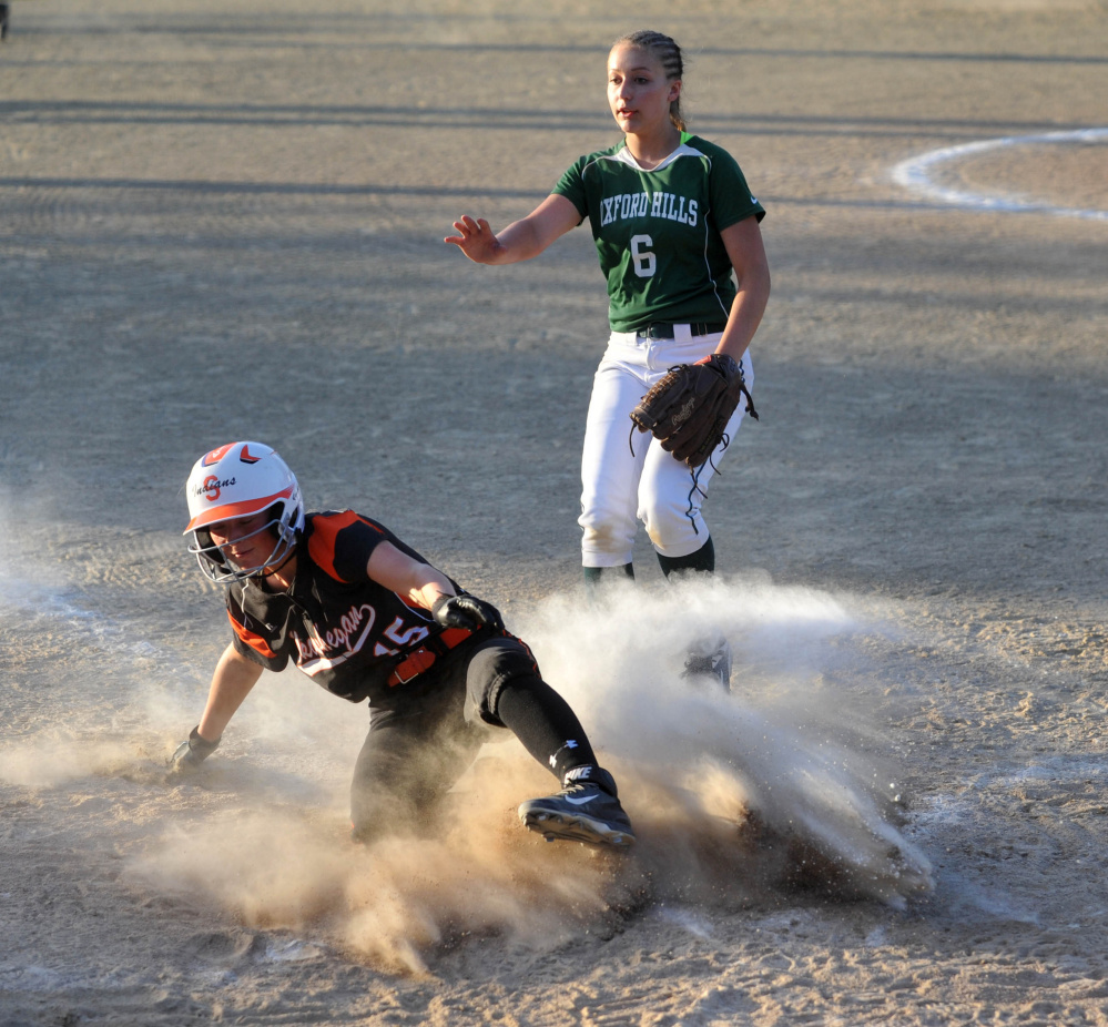Skowhegan's Wylie Bedard scores on a wild pitch as Oxford Hills pitcher Lauren Merrill holds her hand up to stop the throw during the Class A North title game Wednesday night in Augusta.