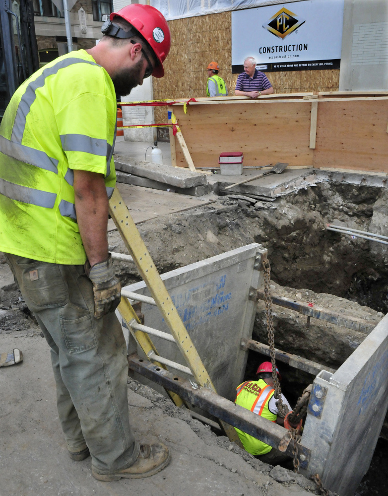 Bob Pellerin, back center, watches workers install new water lines May 24 at 173 Main St. in Waterville. On Monday, traffic on Appleton Street will be allowed one way only from the drive-thru exit of TD Bank to Front Street while work progresses on water pipes.