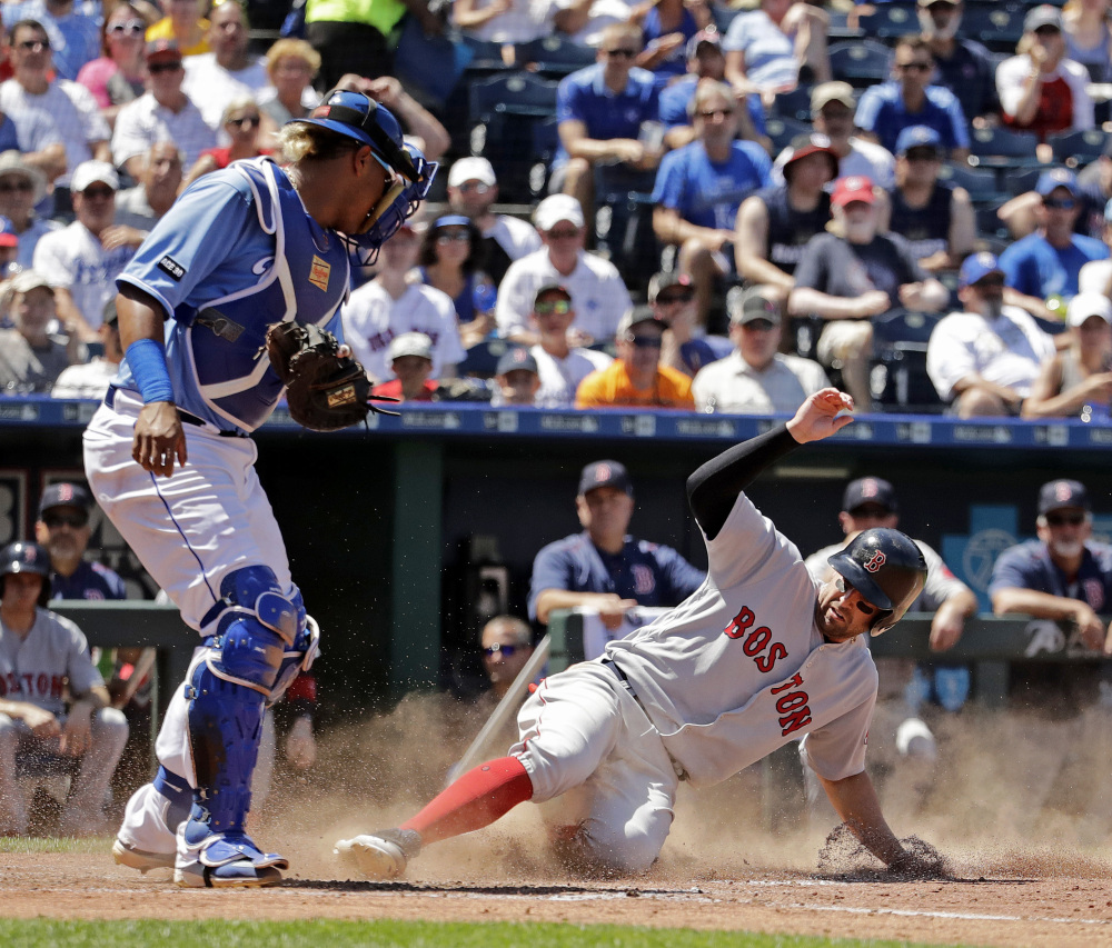 Boston Red Sox infielder Deven Marrero beats the tag by Kansas City catcher Salvador Perez to score on a catching error by first baseman Cheslor Cuthbert during the fifth inning Wednesday.