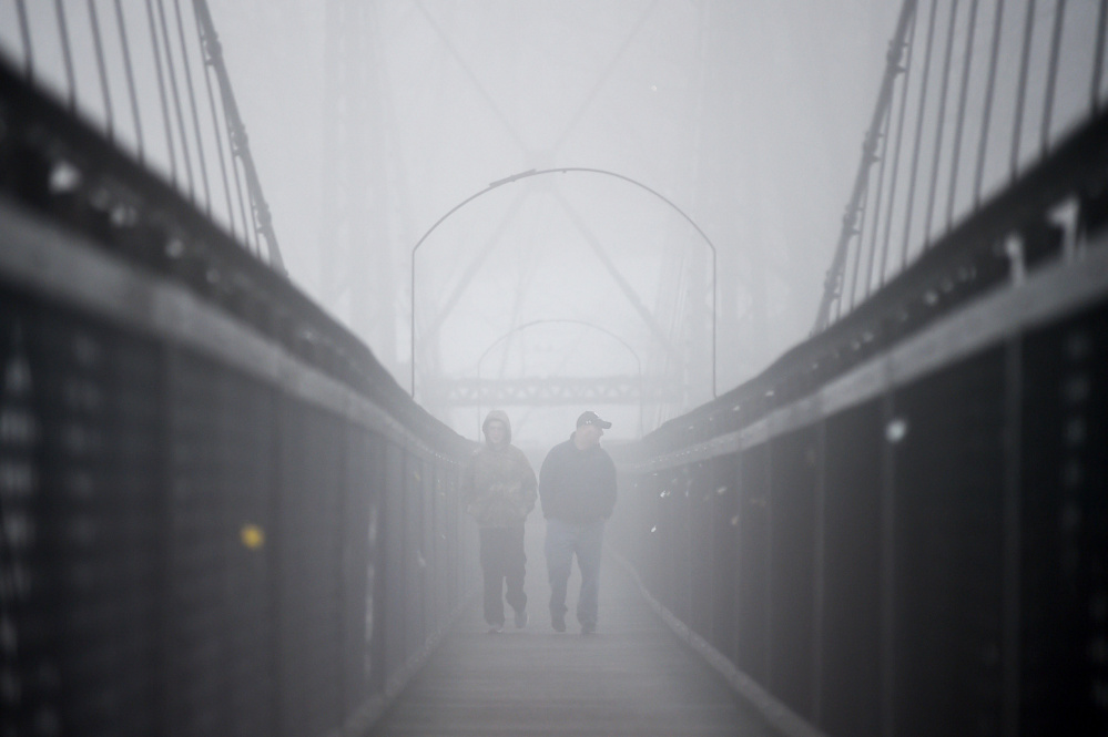 Two people walk across the Two Cent Bridge on March 1 over the Kennebec River as a thick fog settles on Waterville.