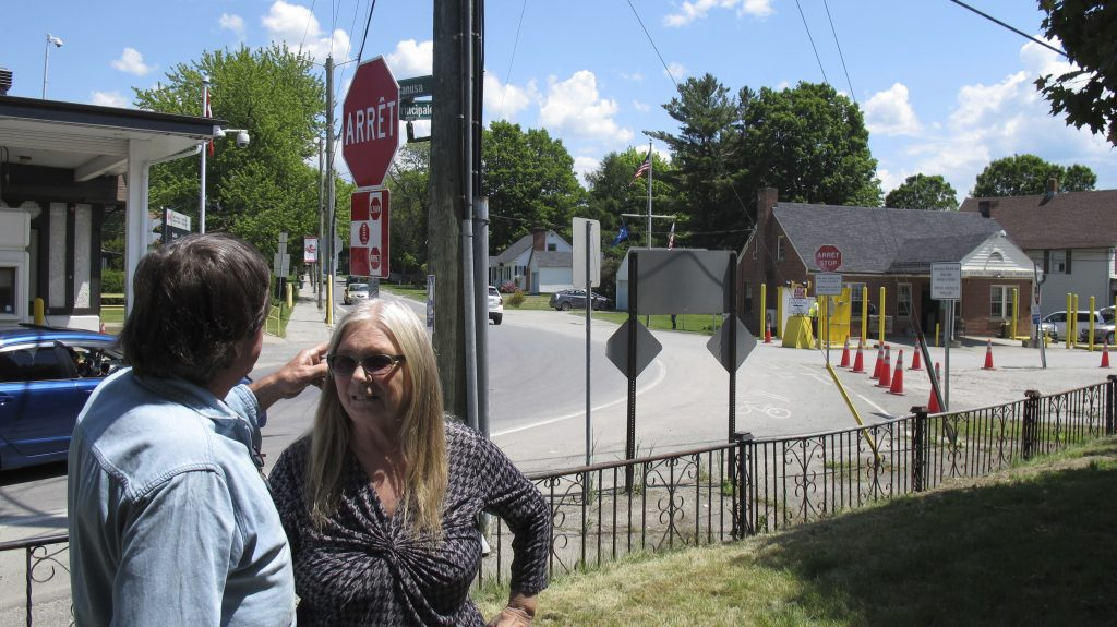 Brian and Joan DuMoulin stand in front of their apartment building that straddles the U.S.-Canadian border. To the left is a Canadian border post, and to the right, a U.S. post.