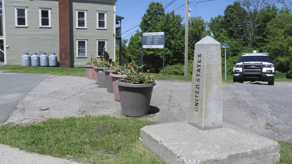A border post and planters show the U.S.-Canadian border where it passes through an apartment building located in the two countries.