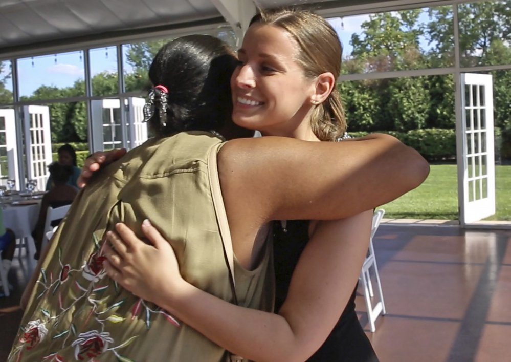 Janice Williamson-Cox, left, hugs Sarah Cummins as she and others arrive at the reception.