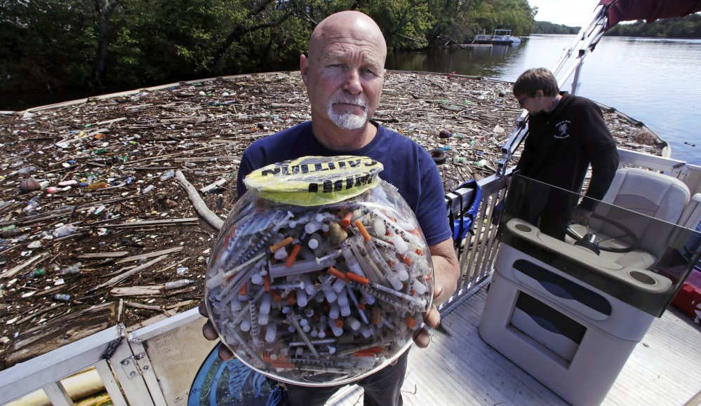 Activist Rocky Morrison of the Clean River Project holds up a fish bowl filled with syringes that were recovered during 2016 on the Merrimack River next to their facility in Methuen, Mass. Morrison leads a cleanup effort along the Merrimack River, which winds through the old milling city of Lowell, and has recovered hundreds of needles in abandoned homeless camps that dot the banks, as well as in piles of debris that collect in floating booms he recently started setting.