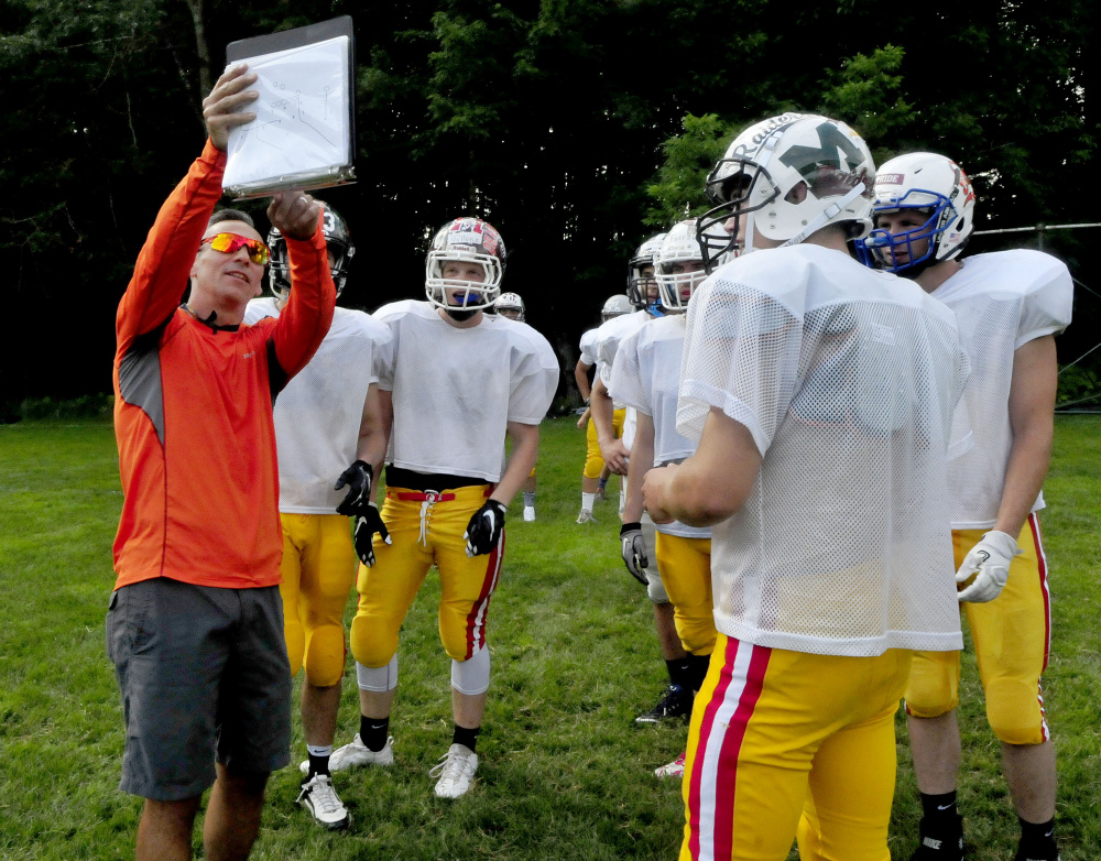 East offensive coordinator Matt Friedman goes over plays with players during Lobster Bowl practice Tuesday at Dover-Foxcroft.