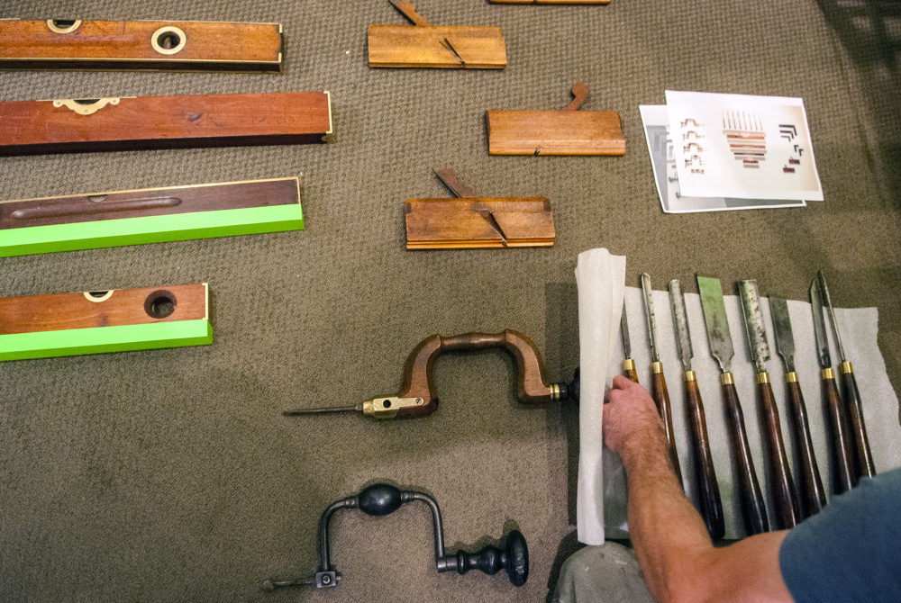 Staff photo by Joe Phelan Ryan Walker, an exhibits preparator at the Maine State Museum, arranges chisels while building a display Tuesday in the entryway to the