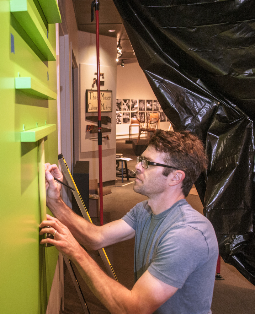 Staff photo by Joe Phelan Ryan Walker, an exhibits preparator at the Maine State Museum, builds shelves for levels and other tools in the entryway to the