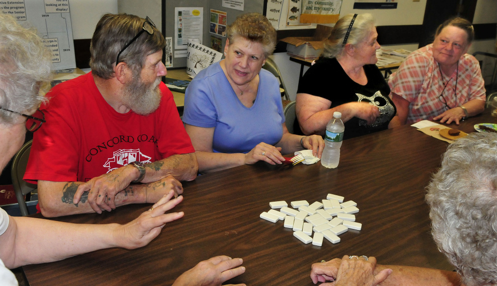 Paula Knox, second from left, asks a question while learning to play dominoes along with Victor LeCourt, Agnes Totherow and Debra LeCourt at the Senior Gathering in Skowhegan on Wednesday.