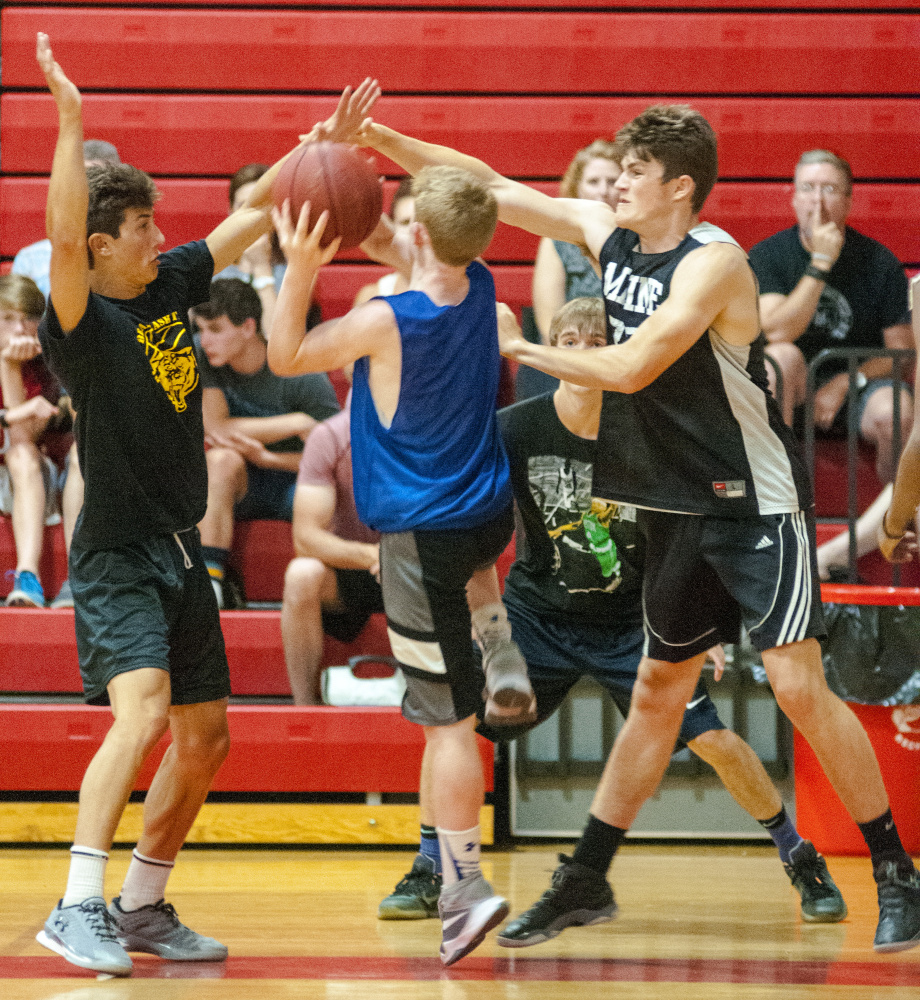Maranacook's Jackson McPhedran, left, and Silas Mohlar, right, double-team Lawrence's Jackson Dudley during a summer league game Wednesday at Cony High School in Augusta.