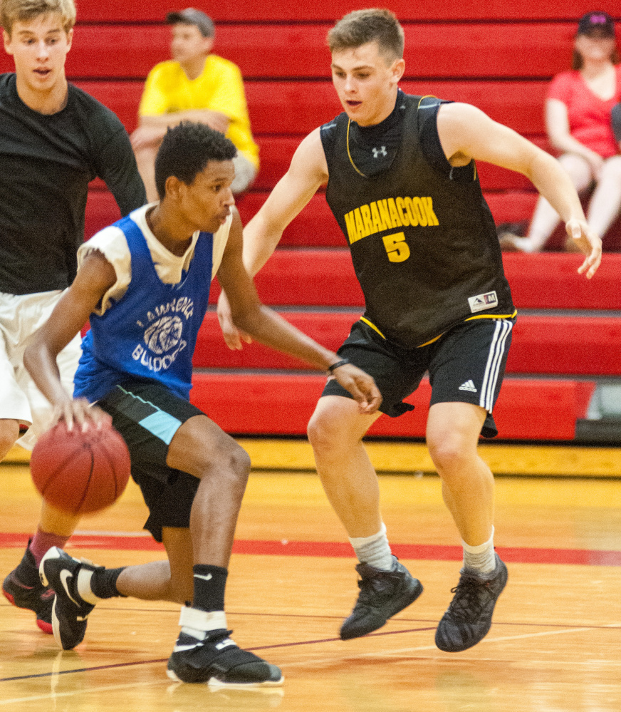 Lawrence's Raheem Goodwin, bottom left, tries to get around Marancook's Jake Patterson during a summer league game Wednesday at Cony High School in Augusta.