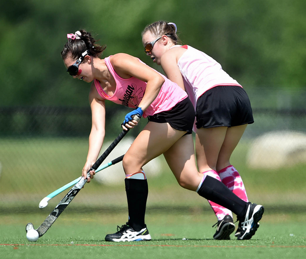 Staff photo by Michael G. Seamans   Skowhegan's Maliea Kelso (2) battles for the ball with a player from Spruce Mountain during the 7th annual Battle for Breast Cancer field hockey tournament Saturday at Thomas College in Waterville.