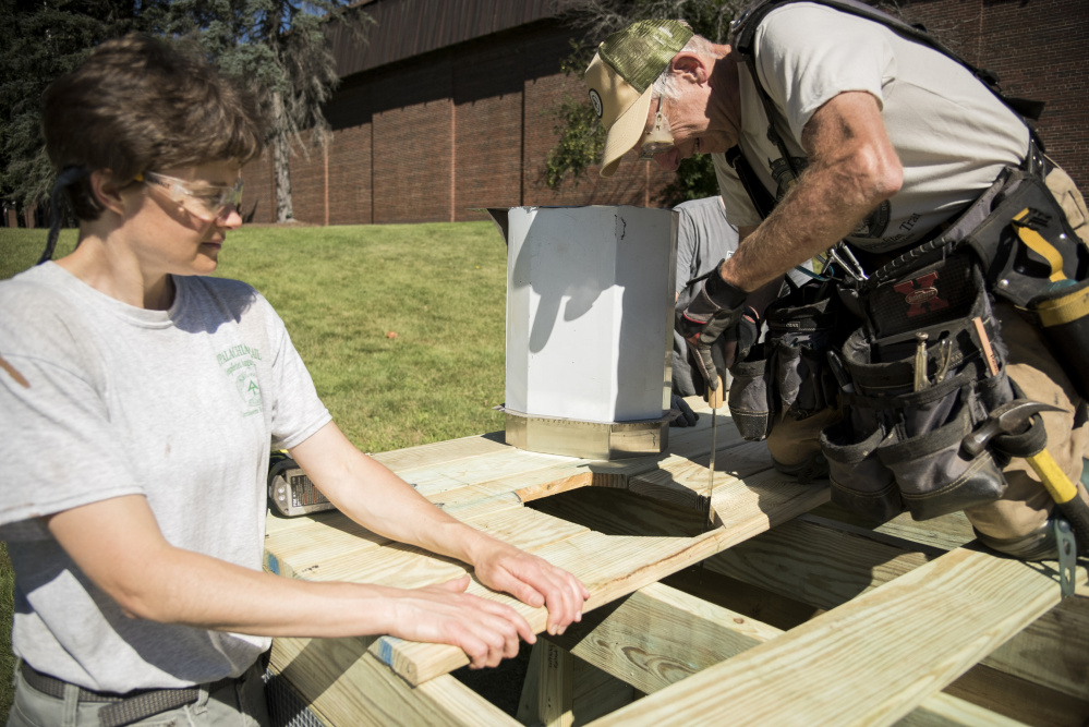 Laura Flight, left, of Readfield, and Dana Humphrey, of Palmyra, construct a privy built as a demonstration project for the Appalachian Trail Conservancy Conference held at Colby College in Waterville.