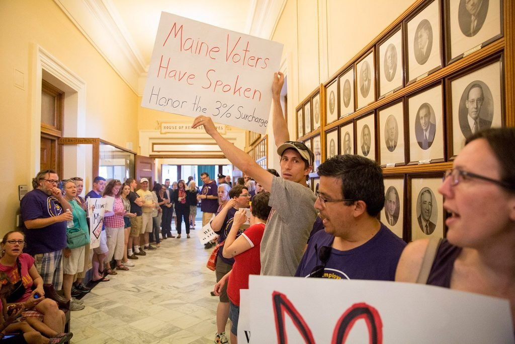 In a protest at the State House on July 3 – the third day of the state government shutdown –  Tom Gilbert of Topsham holds up a sign in favor of the voter-approved 3 percent tax surcharge on the state's highest earners. Later that day, the Legislature passed a budget that dropped the surcharge.