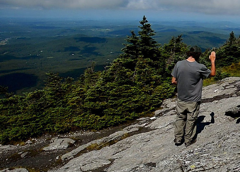 Adam Joseph of the Green Mountain Club talks to hikers new to Vermont's Mount Mansfield in July.