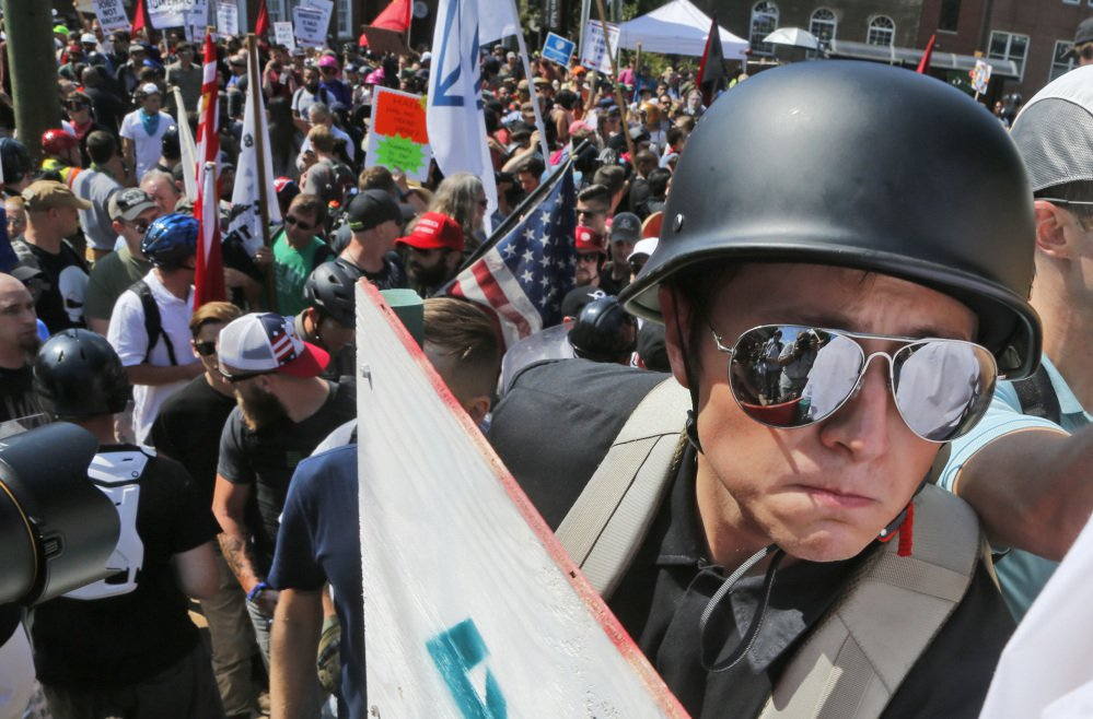 A white nationalist demonstrator with a helmet and shield walks into Lee Park in Charlottesville, Va., Saturday. Hundreds of people chanted, threw punches, hurled water bottles and unleashed chemical sprays on each other after violence erupted at a white nationalist rally in Virginia. At least one person was arrested.