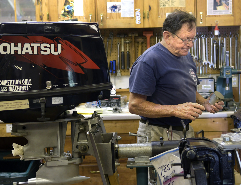 Alex Poliakoff carries a coated piston shaft for an engine he's building for a race boat on Wednesday at his shop in Bowdoinham.