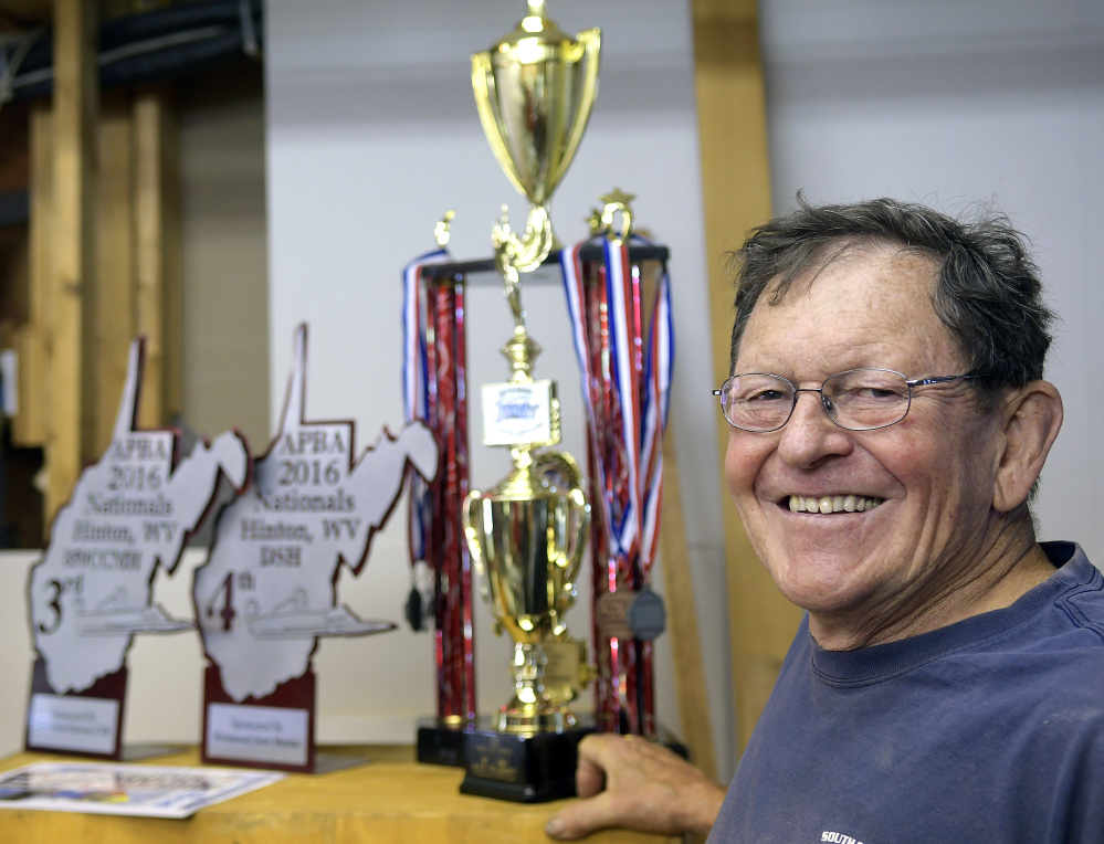 Alex Poliakoff with boat racing trophies he's won at his shop in Bowdoinham.