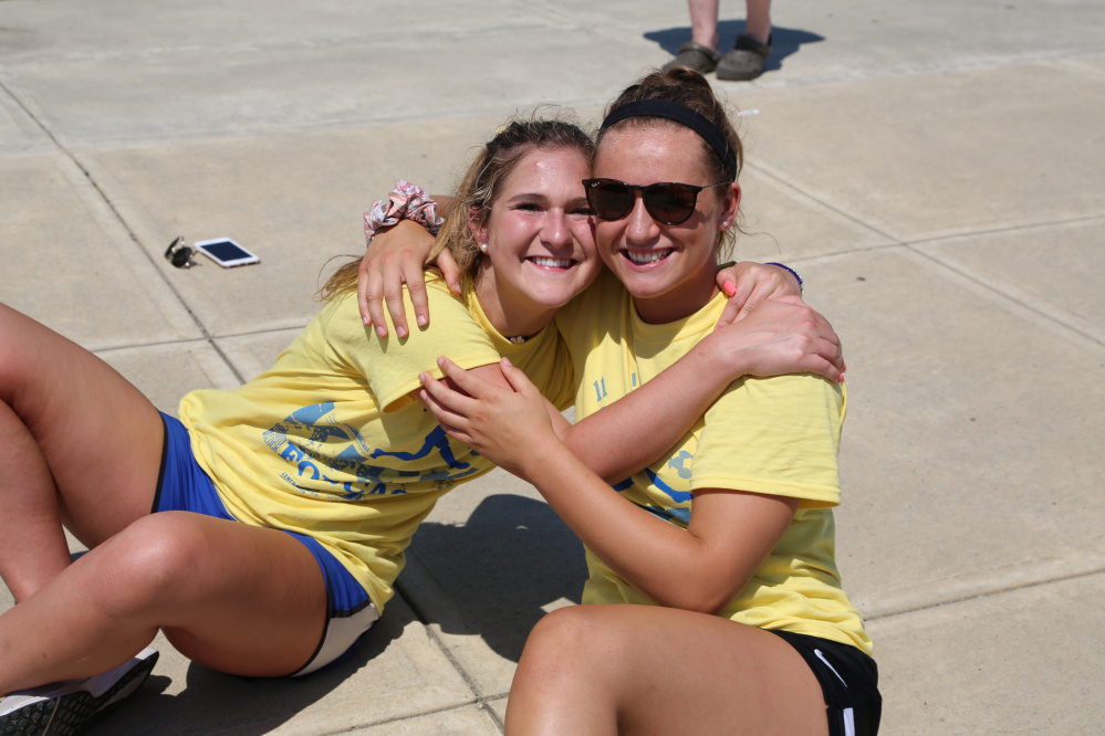 Emily Hogan and Riley Field, Messalonskee graduates of the class of 2016 and event co-chairwomen of Kick Around the Clock for Cass, take a break from playing in the 11-hour soccer game to honor their classmate and friend Cassidy Charette.