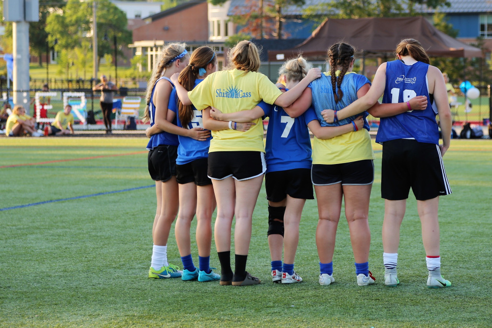 Messalonskee former and current soccer players pause for a moment of silence at the second annual Kick Around the Clock for Cass. The event attracted 450 players and raised more than $10,000 for the ShineOnCass Foundation in memory of Cassidy Charette.