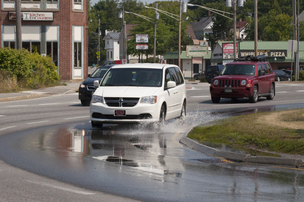 Drivers navigate water puddling on the north side of the Cony Circle on Friday, the result of a water pipe leak that the Greater Augusta Utility District was working Saturday and Sunday.