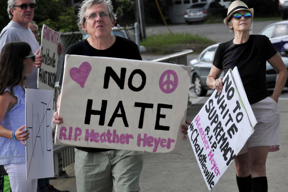 Mark Roman and Lisa Savage hold signs among protesters with Stand With Charlottesville Against White Supremacy during an anti-racist rally in Skowhegfan on Sunday.