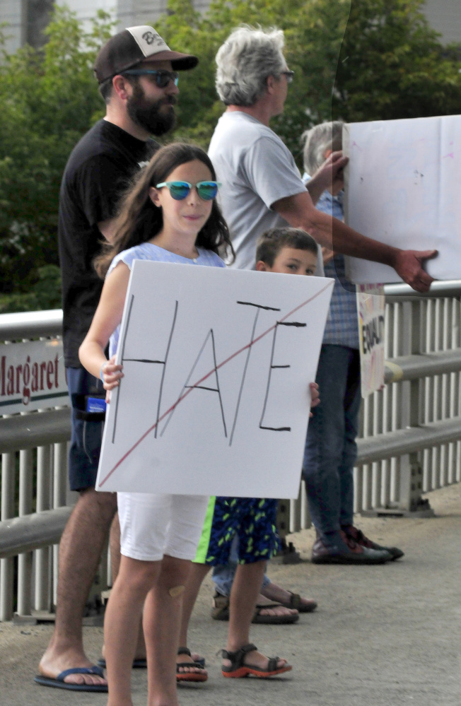 Carly and Finn McCabe and their father, Jeff, hold signs among protesters with Stand With Charlottesville Against White Supremacy in Skowhegan on Sunday.
