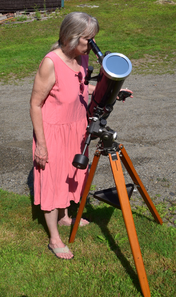 Bonnie Woellner watches the partial solar eclipse Monday afternoon through the Earth-based 4.5-inch Newtonian reflector telescope located in Troy.