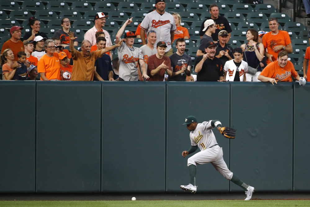 Oakland Athletics left fielder Rajai Davis chases after a fly ball single that hit by Baltimore Orioles' Chris Davis in the second inning Monday.