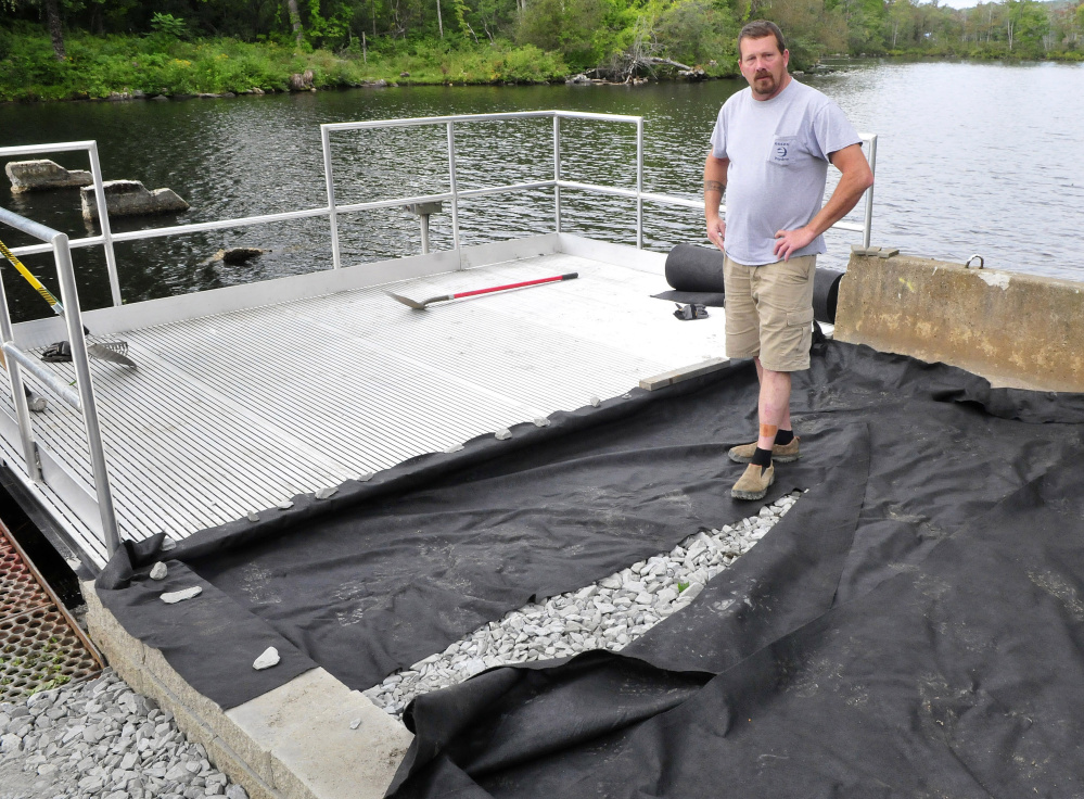 Mike Joslyn, of Messalonskee Stream Hydro, who helped build a fishing platform at the outlet of Messalonskee Lake in Oakland that meets the standards of the Americans with Disabilities Act, explains Thursday that access will be paved from a designated parking spot to the platform.