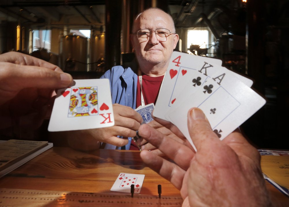 Eldon Woodman lays down a king of hearts while playing cribbage with Ken Capron at Banded Horn Brewing Co. in Biddeford on Thursday. Capron lobbied to get state gaming regulations changed to simplify the organizing of charitable cribbage tournaments. The resulting Great State of Maine Cribbage Tournament will play out at locations around the state this month.
