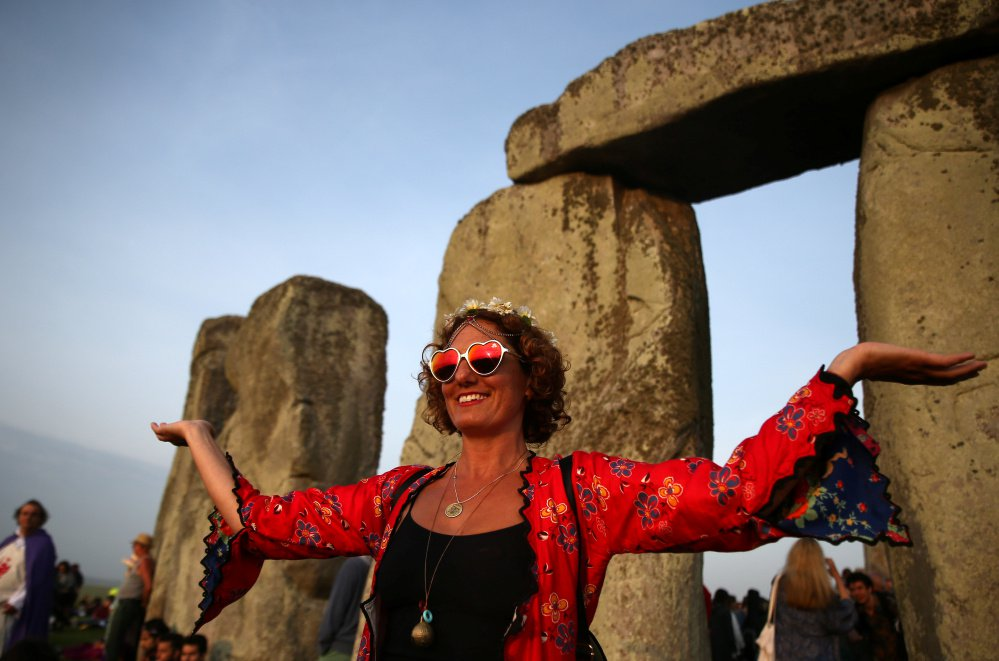 A woman watches the sunrise at Stonehenge on the summer solstice, June 21, near Amesbury, Britain.