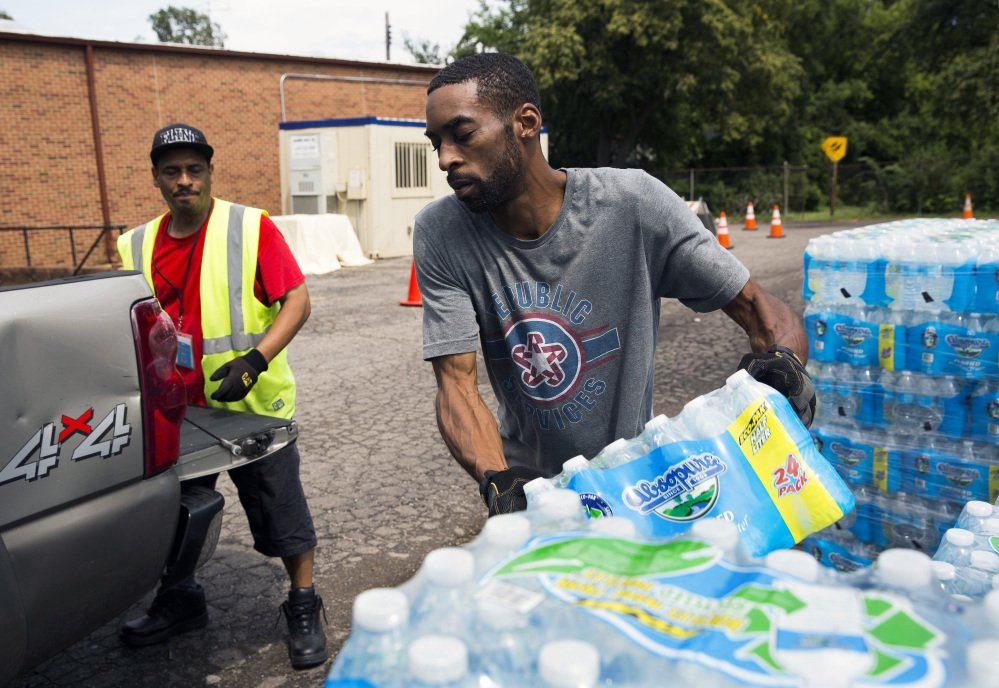 Shawn Jones, right, and Tony Price distribute bottled water last month in Flint, Mich.