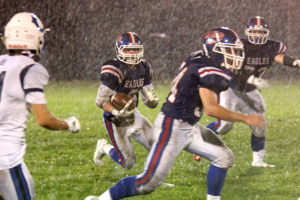 Messalonskee fullback Austin Pelletier looks for some running room in a driving rain during first-half action action against Kennebunk in Oakland on Friday night.