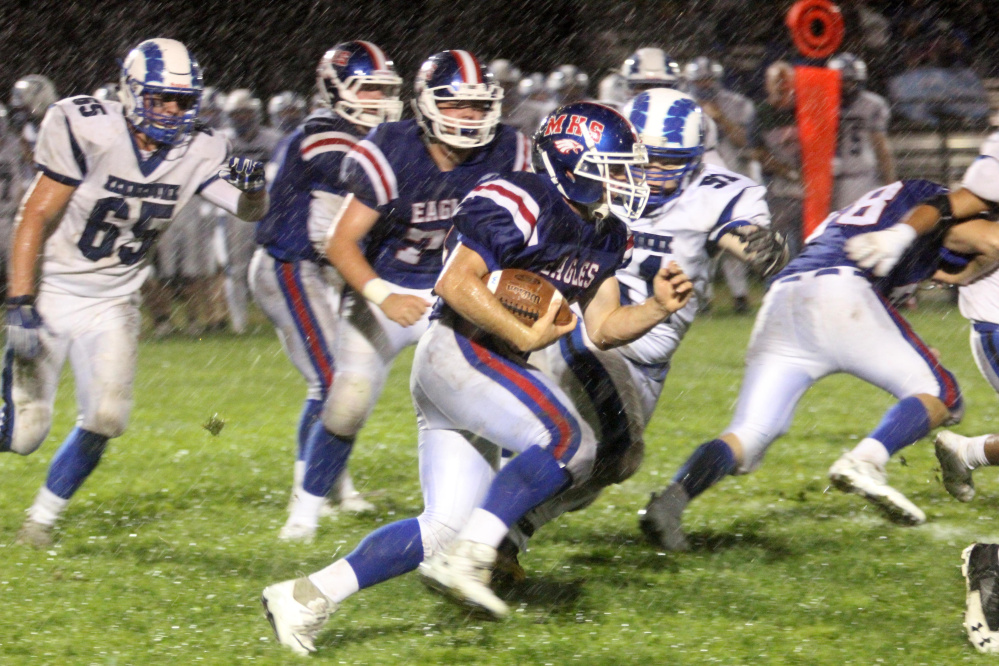 Messalonskee's Alden Balboni tries to elude a tackle by Kennebunk's Brede Gibson during first-half action in Oakland on Friday night.