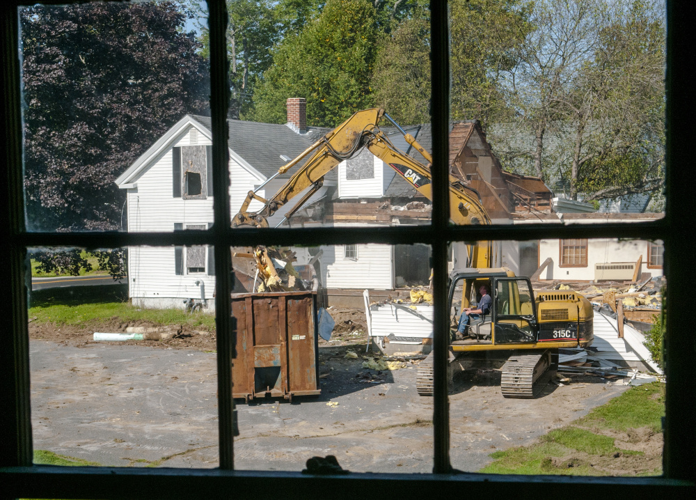 Framed through a window of the Stevens Building, excavator operator Scott Stackpole tears down the Farwell Building on Tuesday at Stevens Common in Hallowell. City planning board members on Wednesday considered the final designs for the new station, which will be built where the Farwell Building once stood.