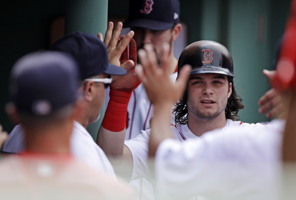 Boston Red Sox outfielder Andrew Benintendi is congratulated by teammates after scoring on a double by Mitch Moreland during the sixth inning of a game against the Athletics on Thursday at Fenway Park in Boston.