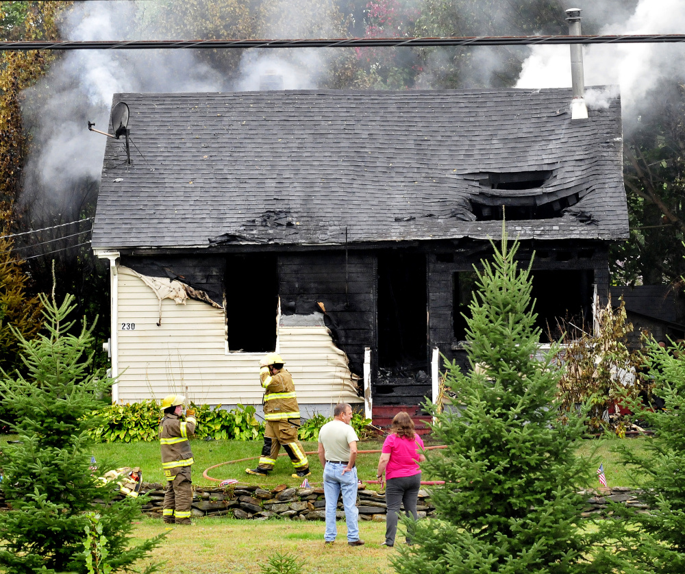 A couple watches as firefighters extinguish a blaze that destroyed the home at 231 Lakeview Drive in China on Monday.