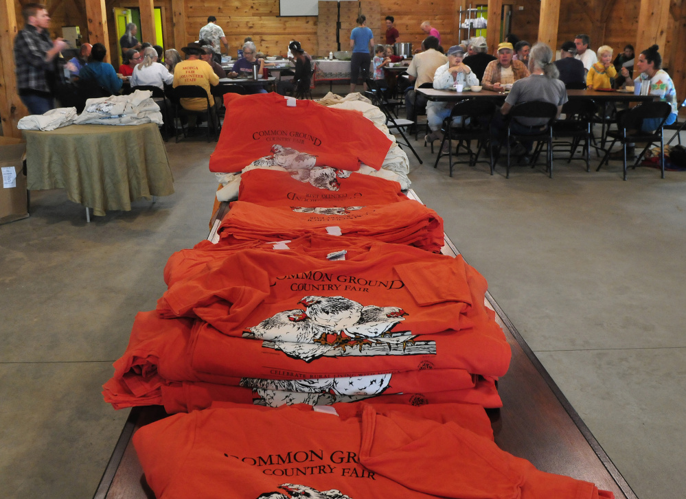 Some of the 2,850 volunteers have lunch near piles of T-shirts for the Maine Organic Farmers and Gardeners Association 41st annual Common Ground Country Fair in Unity on Monday. The fair runs this Friday through September 24.