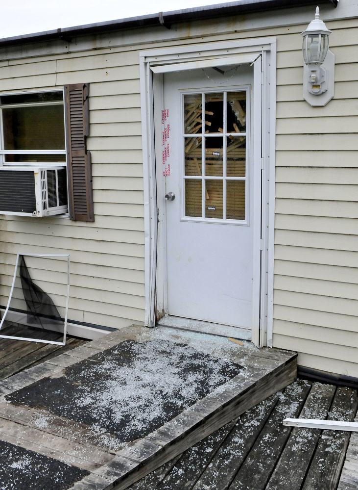 Glass from a shattered window in a door that is sealed with police evidence tape is seen at the front entrance to a mobile home at 1003 Oakland Road in Belgrade on May 22. Homeowner Roger Bubar died in a police officer related shooting on May 20 and his son Scott Bubar was seriously wounded and later arrested in connection with the shooting.