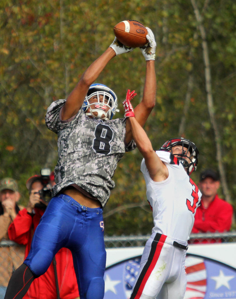Oak Hill High School's Darryn Bailey grabs a 25-yard pass from quarterback Gavin Rawstron over Wells High School's Christian Saulnier during first-half action in Wales on Saturday.
