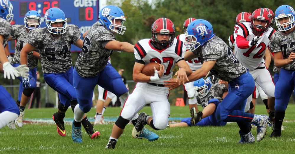 Wells High School's Chad Fitzpatrick runs past Oak Hill High School's Bailey Drouin, left, and Cruz Poirier, right, during a first-half carry in Wales on Saturday.