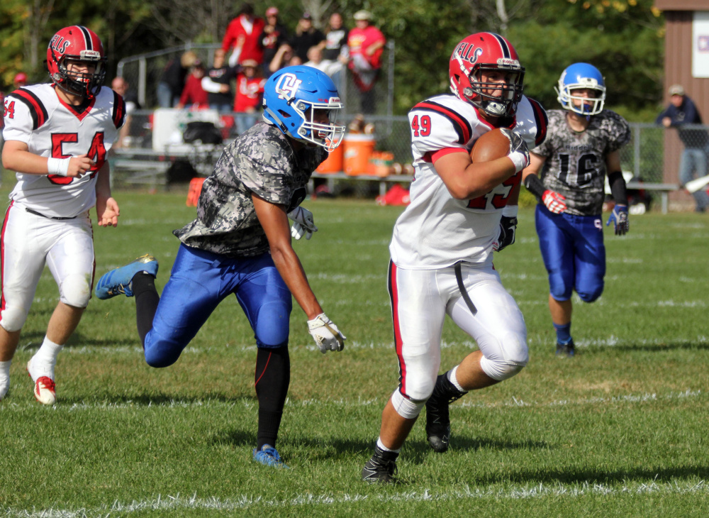Wells High School's Nolan Potter runs past Oak Hill High School's Darryn Bailey for a 19-yard touchdown in the first half in Wales on Saturday.