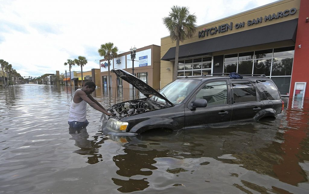 John Duke tries to figure out how to salvage his flooded vehicle in the wake Hurricane Irma, Monday in Jacksonville, Fla.