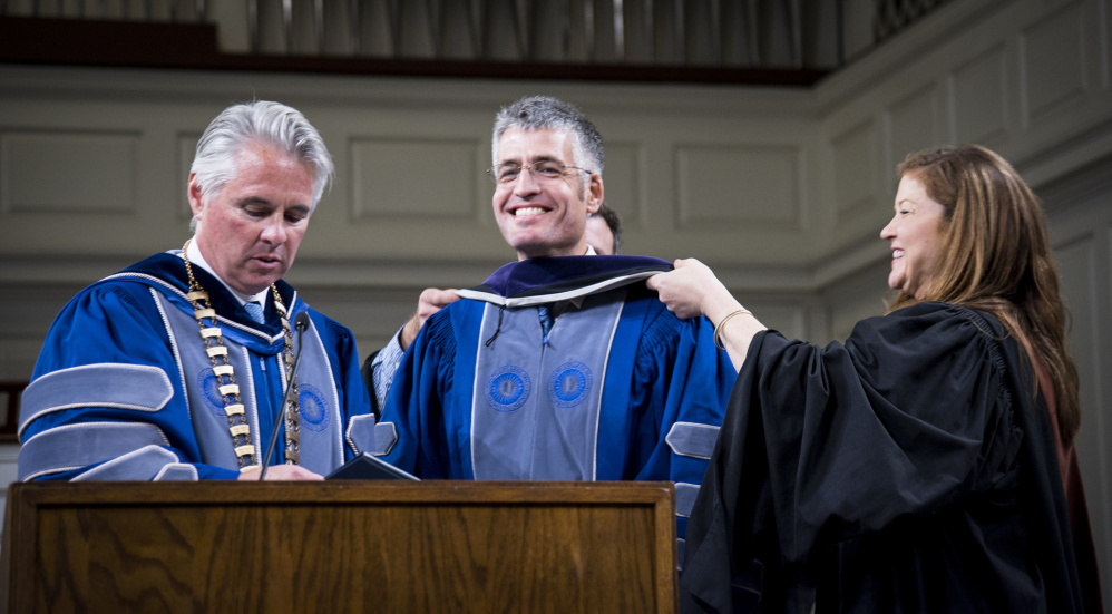 Colby College Marshal Annie Kloppenberg, right, assists in placing an honorary degree hood on Lovejoy Award Recipient Alec MacGillis, center, at Convocation ceremonies on Monday night at Lorimer Chapel on the college campus as Colby College President David Greene, left, reads the citation.