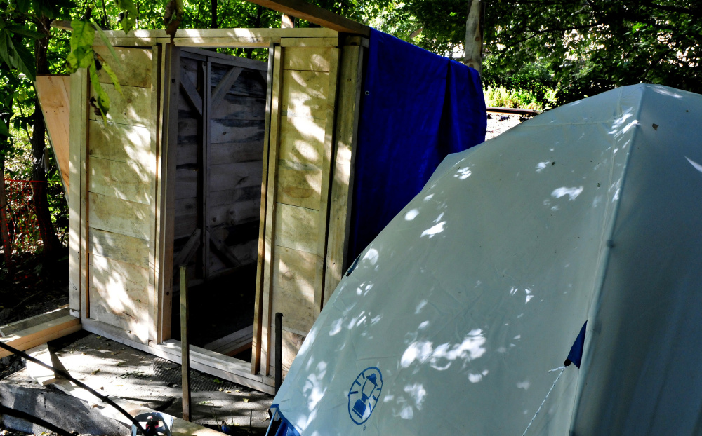 Vaughn Orchard, who is homeless and was living in a tent near Pan Am Railways train tracks in Waterville, has been charged with criminal trespass. Recently a wood frame building has been partially erected beside his tent. The train tracks can be seen 50 feet away.