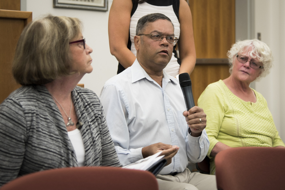 Elliot Kollman, center, of Willow Street, expresses concern Wednesday about a proposed housing development at the former mill site at the end of Maple Street. He said it should remain private property. He is joined by Ward 4 Councilor Anna Blodgett, left, and his wife, Mary Jo.