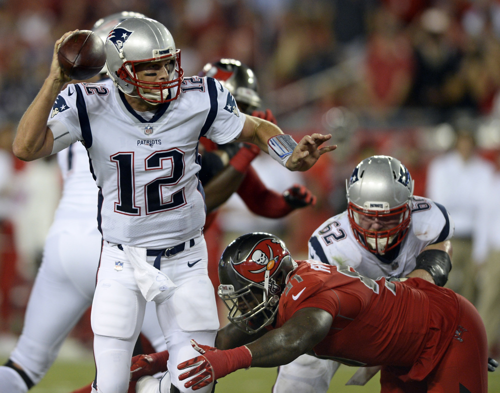 New England Patriots quarterback Tom Brady (12) looks to throw a pass as he is pressured by Tampa Bay defensive end Robert Ayers during the first half Thursday in Tampa.